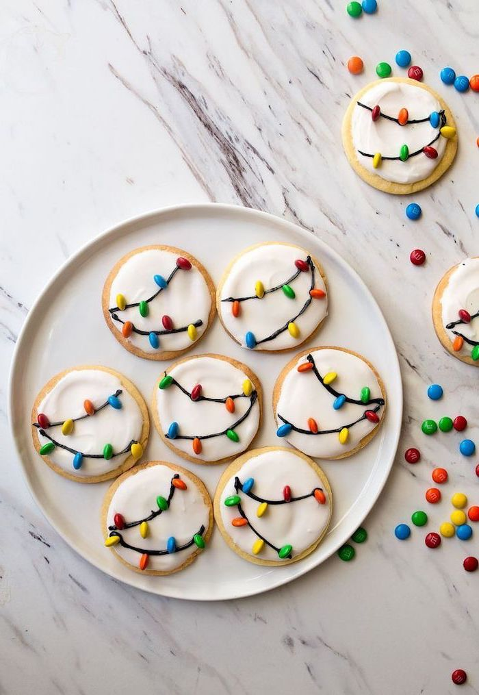 round cookies with white icing, m&ms used for lights, placed in white plate, christmas cookie icing, placed on marble countertop