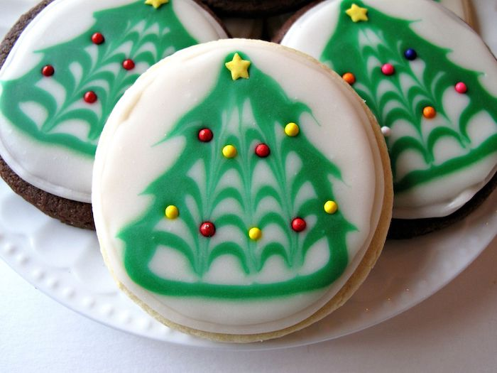 how to make icing for cookies, round cookies with green and white icing, christmas tree drawn on them with icing