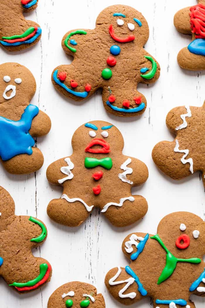 gingerbread men with different faces, colorful icing on top, cookie icing, placed on white wooden surface