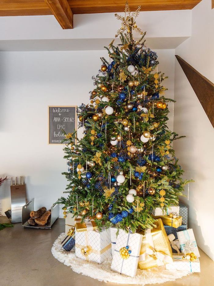 blue white and gold ornaments, tall tree with a star topper, elegant christmas tree decorating ideas, placed on white rug, wrapped presents underneath
