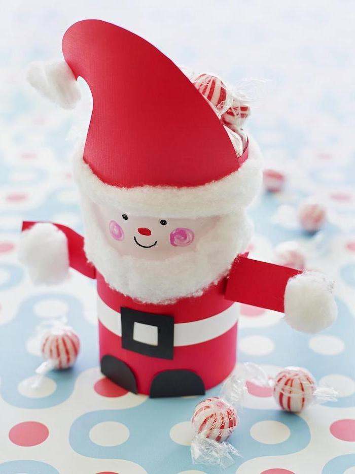 santa made of toilet paper roll, christmas crafts for toddlers age 2 3, painted in red, candies scattered around it
