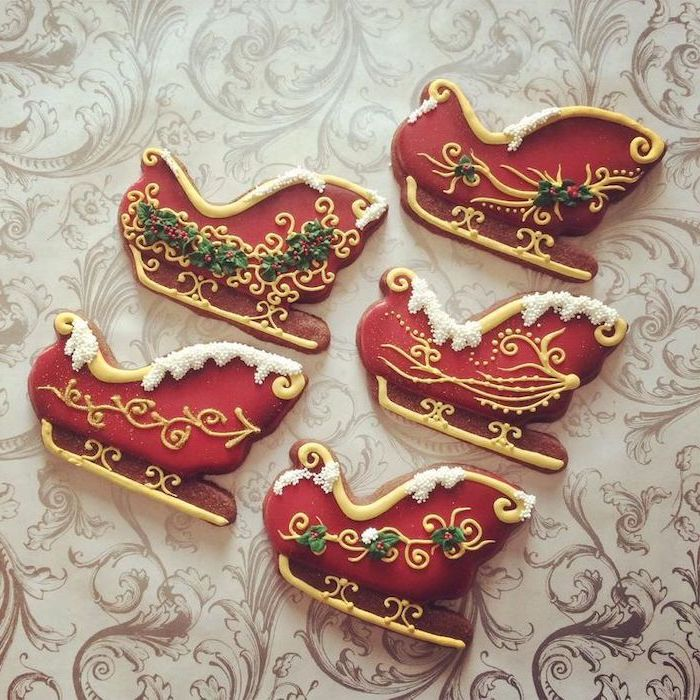 santa's sled shaped cookies, decorated with red green white and gold icing, royal icing christmas cookies, placed on white surface