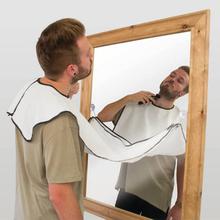 man wearing grey t shirt, shaving apron attached to a mirror, creative gifts for boyfriend, mounted on white wall