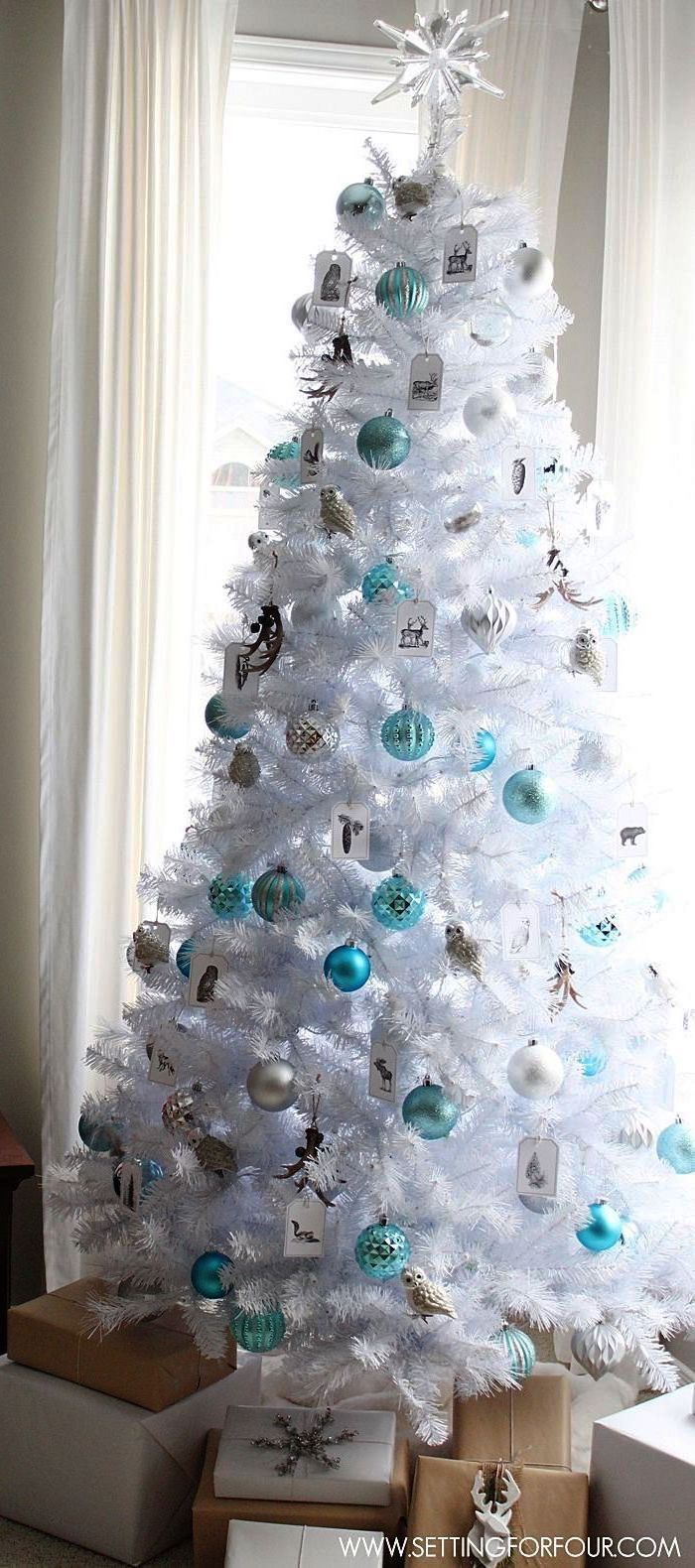 how to decorate a christmas tree with ribbon, white faux tree, silver and turquoise ornaments, wrapped presents underneath