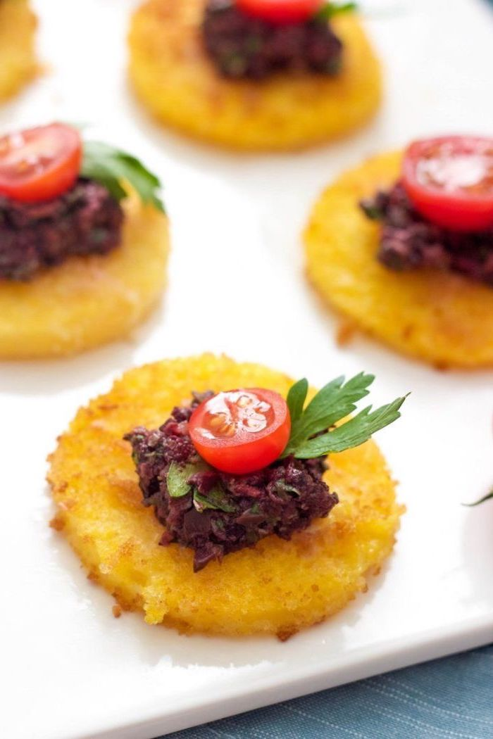 small hash brow bites with beet dip, halved cherry tomatoes on top, arranged on white plate, make ahead christmas appetizers