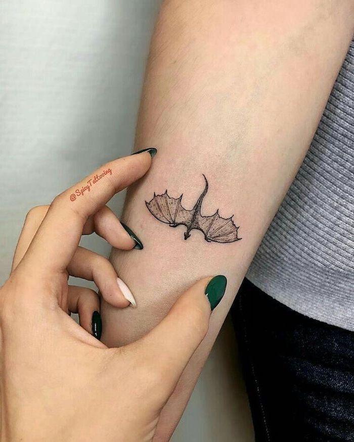 small drargon flying, wrist tattoo, dragon tattoos for women, woman with green nail polish