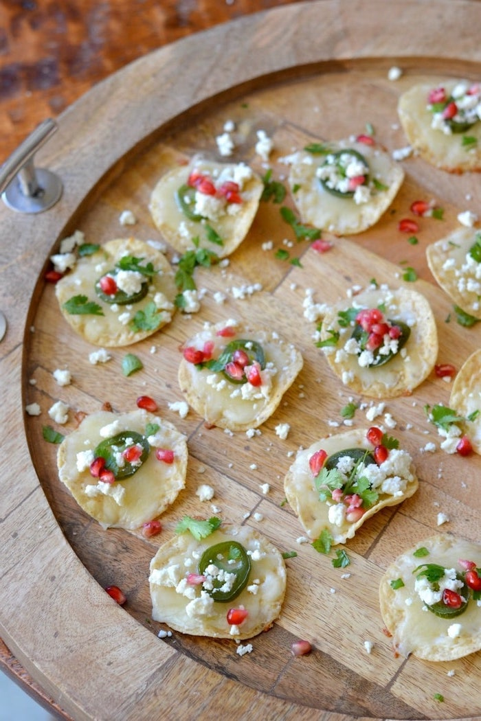small tortilla wraps, cheese and jalapeño, pomegranate seeds and crumbled feta cheese, arranged on wooden tray, make ahead christmas appetizer