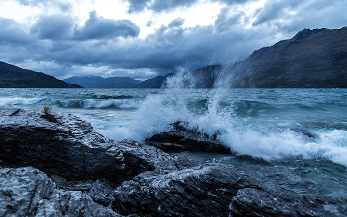 waves crashing into rocks, desktop backgrounds for windows 10, surrounded by rocks and mountain peaks