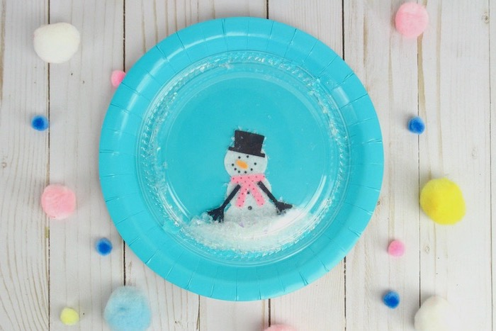 blue paper plate with snowmen drawn on it, plastic lid on top, faux snoq inside, diy ornaments for kids, placed on wooden surface
