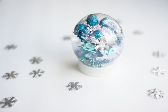 snow globe, with blue and silver pompoms, christmas ornament crafts, placed on white surface, silver snowflakes