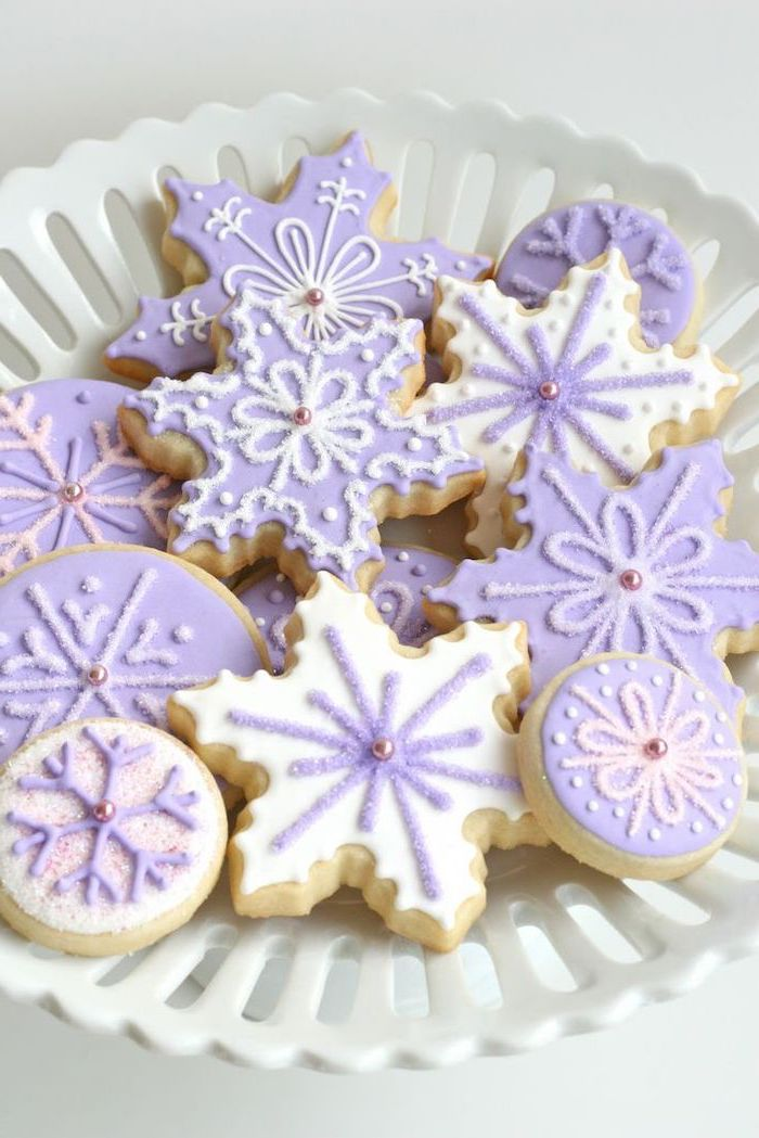 snowflake shaped cookies, decorated with purple and white icing, royal icing christmas cookies, placed in white bowl