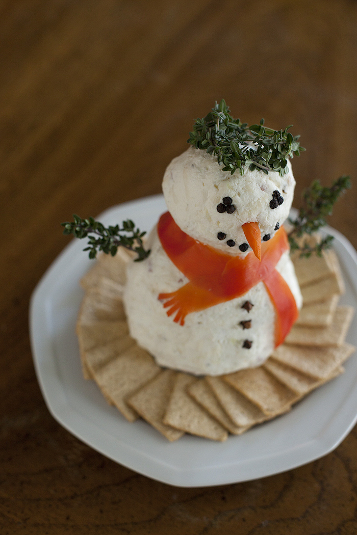 christmas eve appetizers, snowman made of cheeseballs and herbs, crackers on the side, placed on white plate