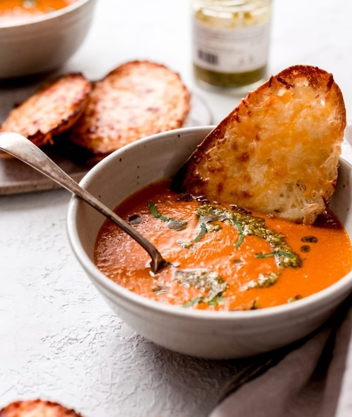 white ceramic bowl, filled with cream soup, cream of mushroom soup recipe, bread dipped in it, pesto sauce garnish
