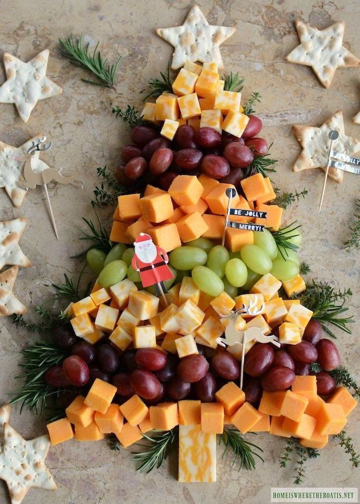 christmas tree made of grapes, different types of cheese, rosemary branches, christmas eve appetizers, star shaped crackers