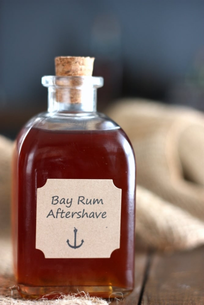 small bottle of bay rum aftershave with cork cap, christmas gifts for boyfriend, placed on wooden surface, step by step diy tutorial