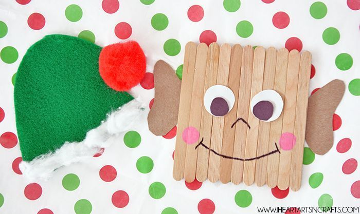 popsicle stick elf, green hat made of felt, christmas crafts for kids, placed on white sheet with red and green dots