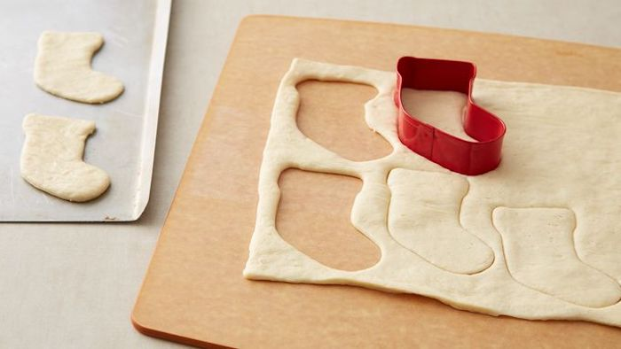 stocking shaped cookie cutter, used on dough, placed on wooden board, holiday appetizers, placed on white surface