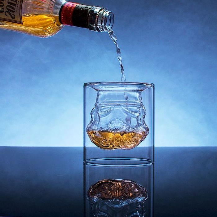 christmas gifts for men, star wars inspired stormtrooper whiskey glass, whiskey poured into it, placed on black surface