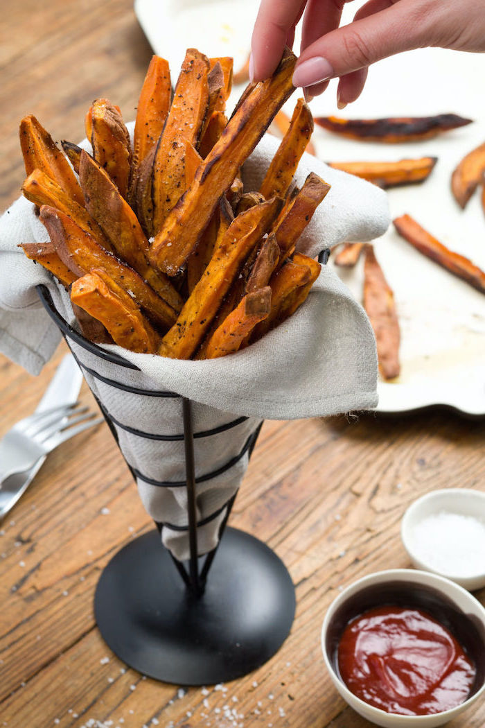sweet potato fries inside a black metal cone, white cloth inside, christmas eve appetizers, placed on wooden surface