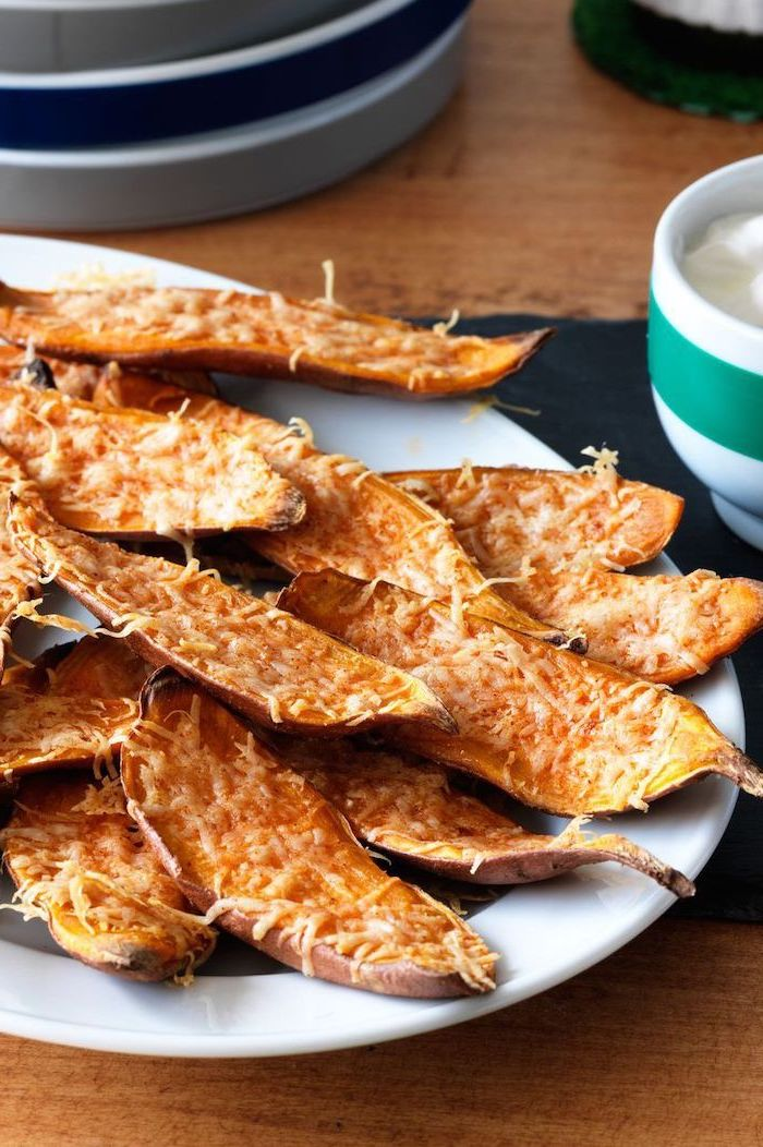 baked sweet potato skins with cheese on top, placed on white plate, christmas eve appetizers, placed on wooden surface