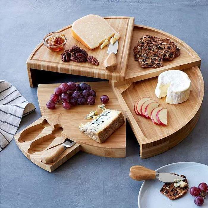 wooden swivel cheese board, gifts for mom from son, different types of cheese fruits and nuts on it, on grey table