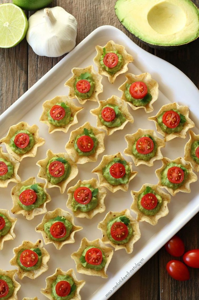 christmas party snacks, small taco shells filled with guacamole, halved cherry tomatoes on top, arranged on white tray