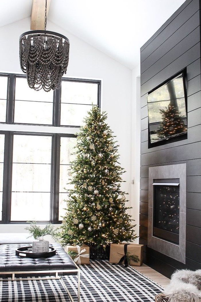 tree placed in the corner with presents underneath, how to decorate a christmas tree with ribbon, decorated with silver and gold ornaments