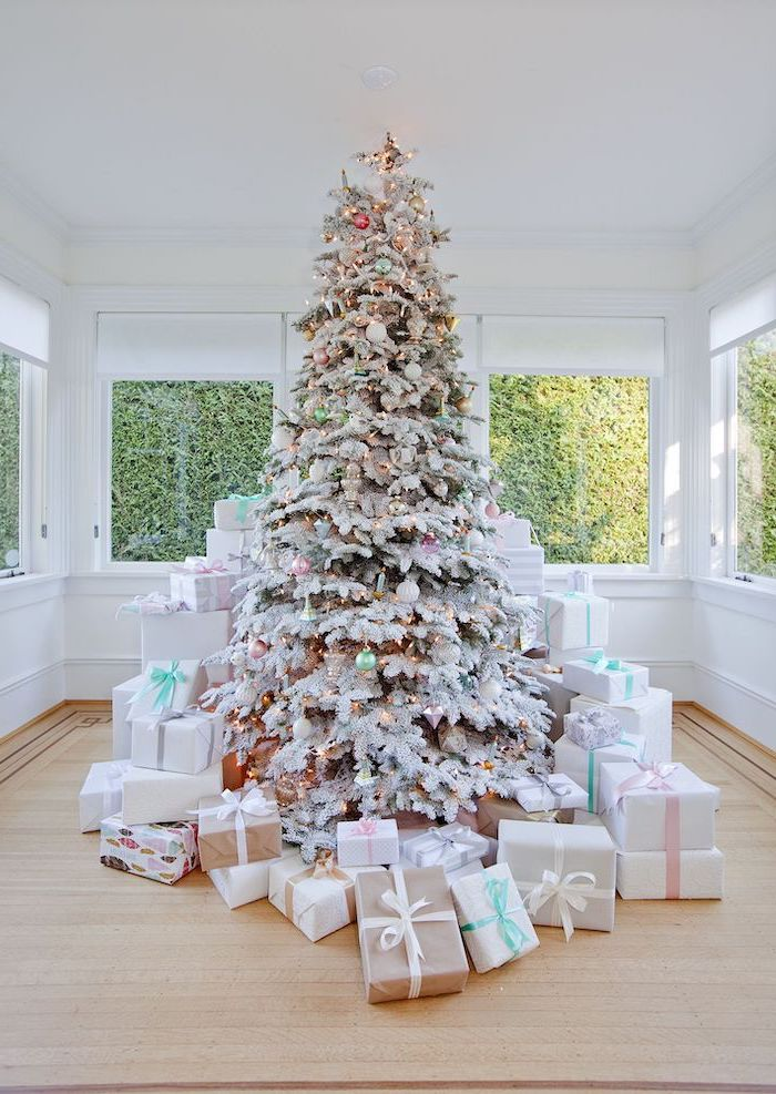 tall tree with faux snow, surrounded by presents, white christmas tree decor, decorated with small ornaments