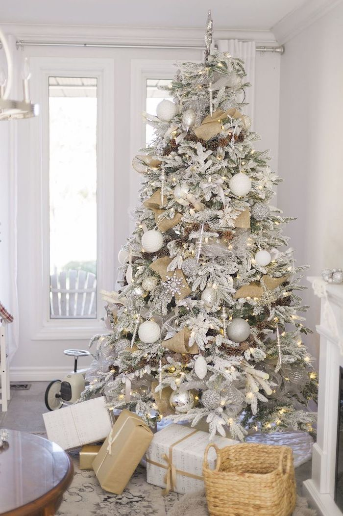 tree with faux snow, decorated with white and silver ornaments, gold ribbon wrapped around, how to decorate a christmas tree with ribbon