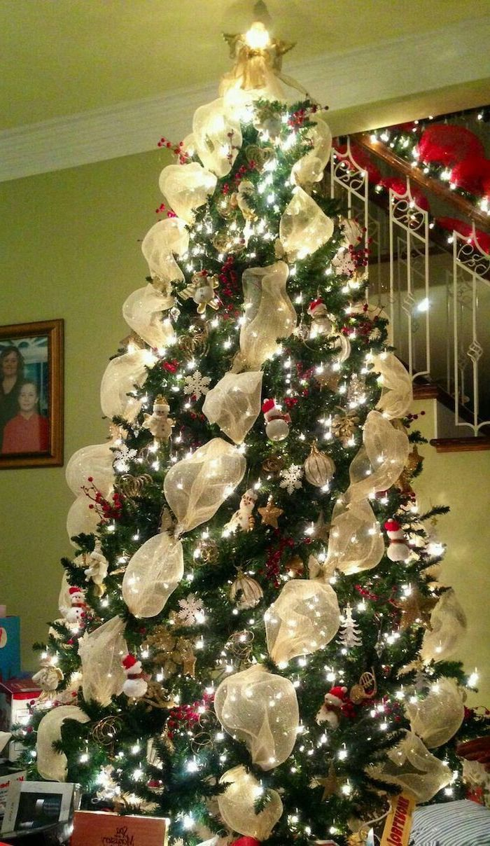 tree decorating ideas, gold ribbon wrapped around a tree, red and gold ornaments, gold star topper