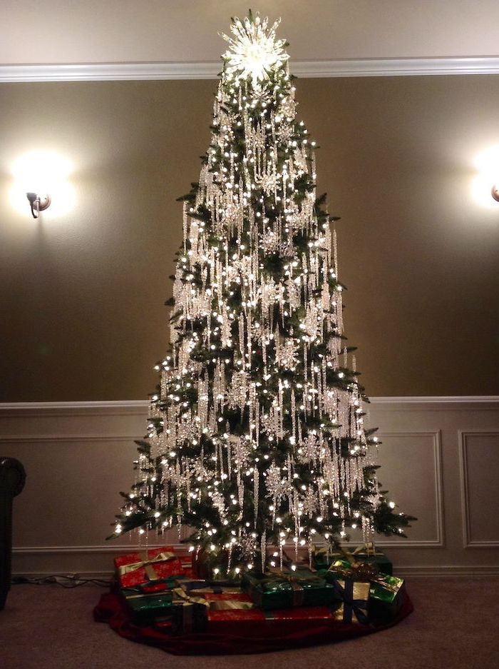 tree with lots of lights, decorated with crystal hanging ornaments, tree decorating ideas, wrapped presents underneath