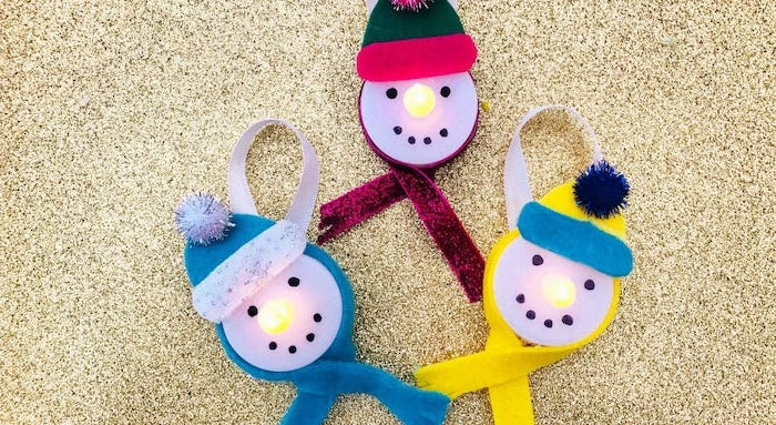 how to make ornaments, tea light snowmen, scarfs and beanies made of felt, placed on gold glittery surface