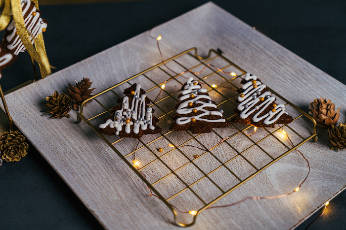 three christmas tree shaped cookies, decorated with royal icing and sugar pearls, vegan gingerbread cookies, placed on metal rail