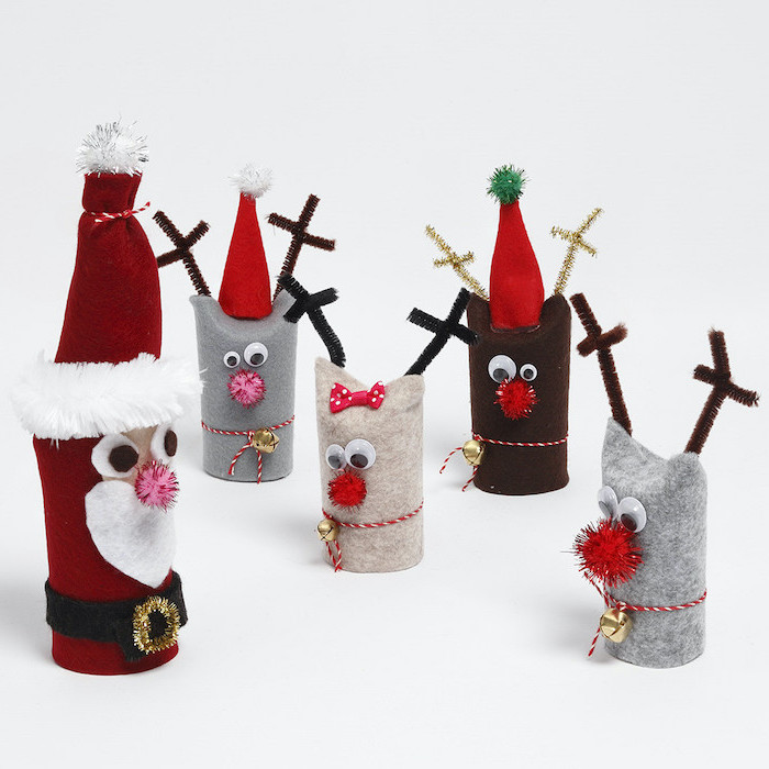 toilet paper rolls covered with felt, turned into santa and his reindeer, christmas crafts for toddlers age 2 3, placed on white surface