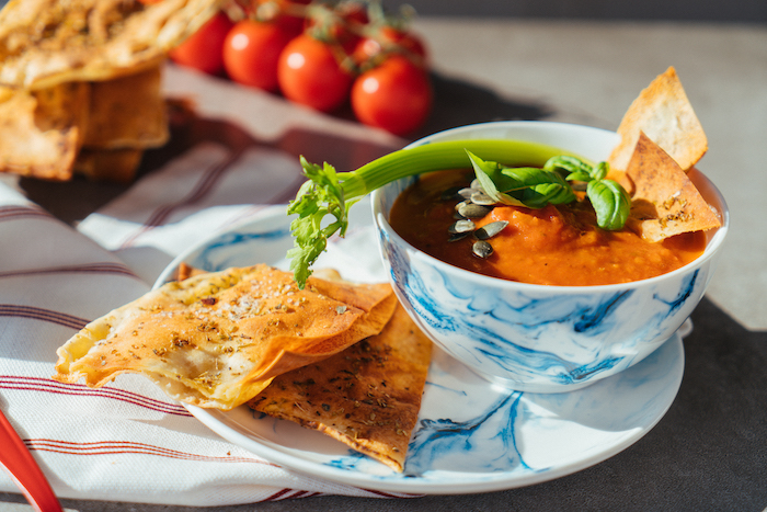 tomato soup recipe, tomato soup inside a ceramic bowl, garnished with seeds celery and basil, bread on the side