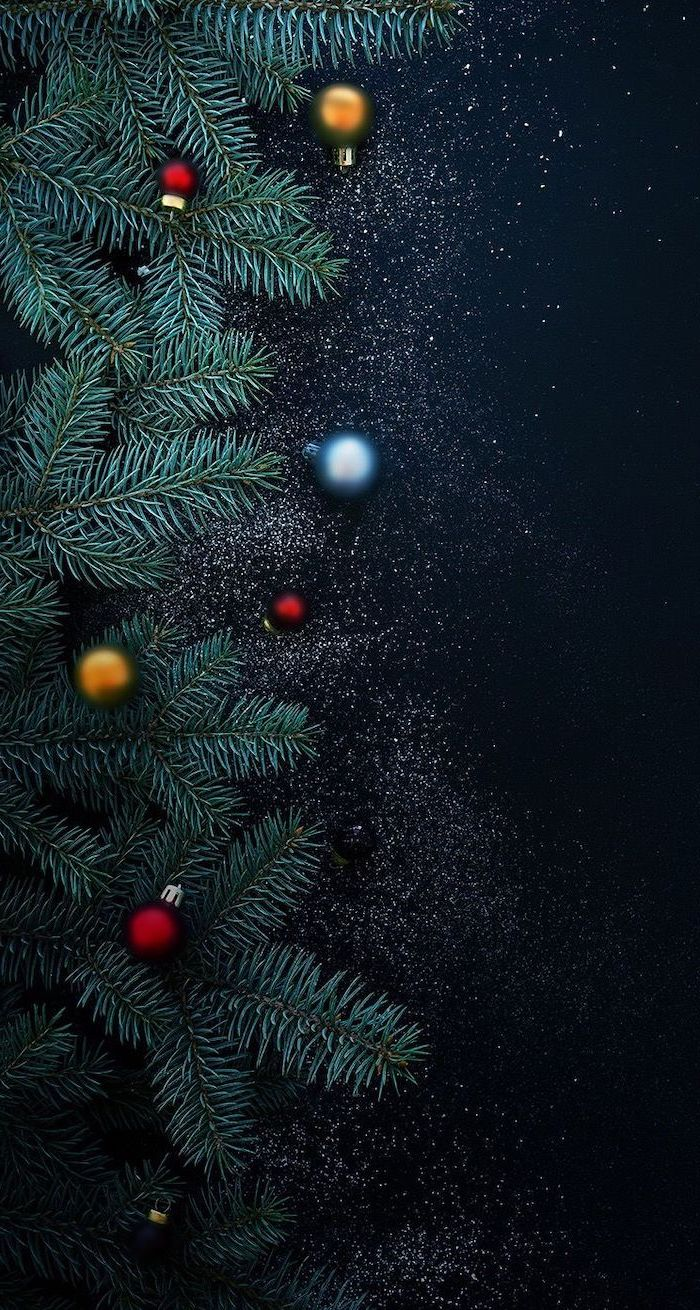tree branches placed on black surface, blue gold and red baubles around them, winter wallpaper iphone