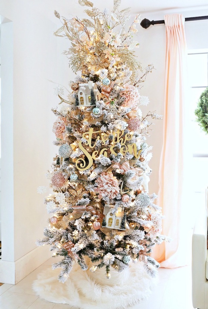 small tree decorated with lots of faux flowers, placed on white rug, white christmas tree decor, next to a tall window
