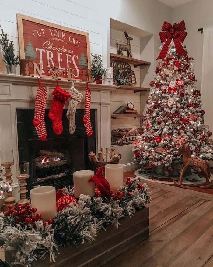 red and silver ornaments, on a tree with faux snow, tree decorating ideas, large red ribbon on top, placed next to the fireplace