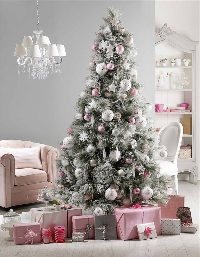 tree with faux snow, decorated with pink and silver ornaments, white christmas tree decor, wrapped presents underneath