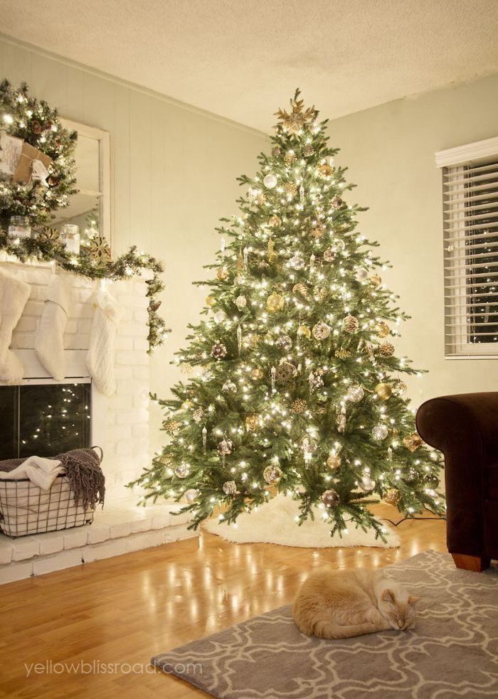 tree decorated with lots of lights, gold ornaments and pine cones, white christmas tree decor, cat sleeping on the floor next to it