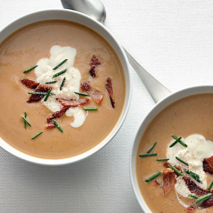 two white bowls, full of cream soup, bacon garnish on top, cream of mushroom soup recipe, white table cloth