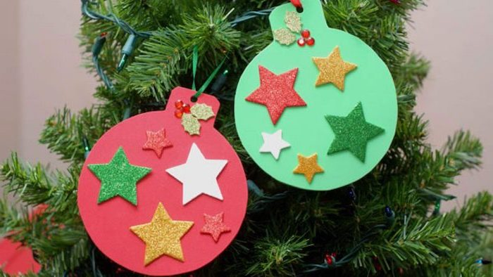 baubles made of red and green paper, colorful glittery stars glued to them, how to make ornaments, hanging on tree with lights