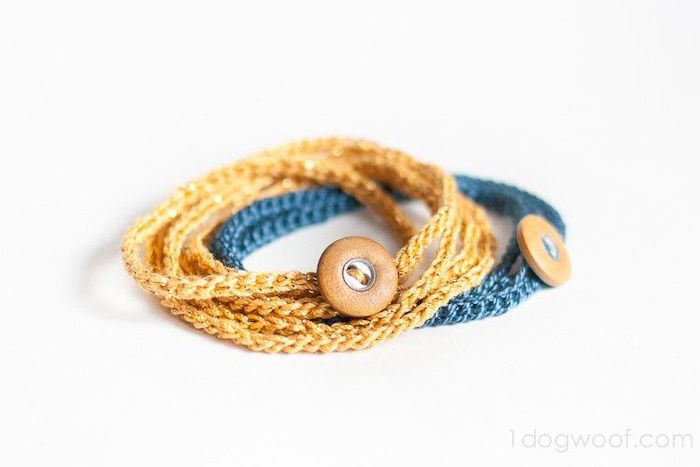 two crochet bracelets in blue and gold, with brown leather buttons, placed on white surface, gifts for boyfriend, step by step diy tutorial