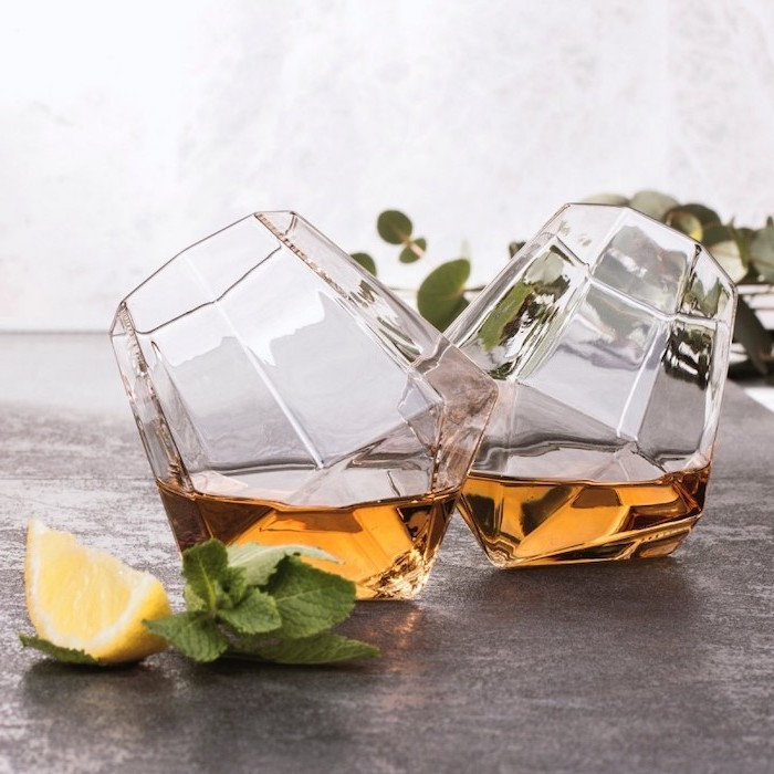 two diamond shaped crystal whiskey glasses, placed on grey surface, christmas gift ideas for him, mint leaves and lemon slices on the side