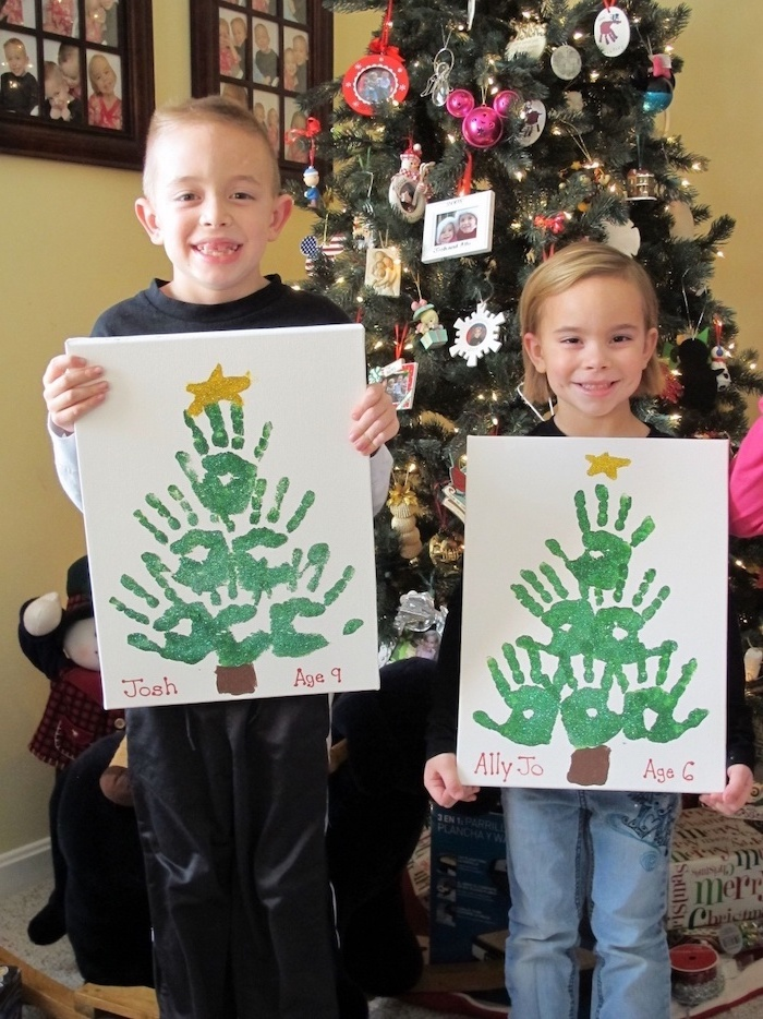 two kids holding canvases, christmas trees made with their handprints, christmas crafts for toddlers age 2 3