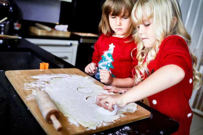 two little girls baking, how to make ornaments, dough rolled out on wooden board, placed on black surface