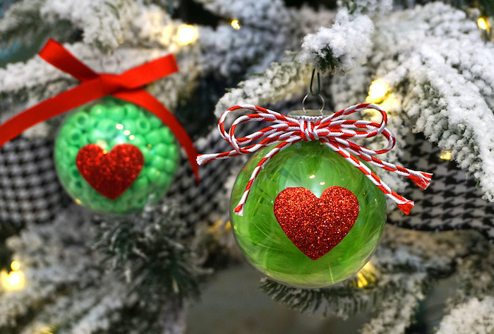 two plastic baubles, filled with green beads, with red glittery hearts, easy christmas crafts for kids, hanged with red bows