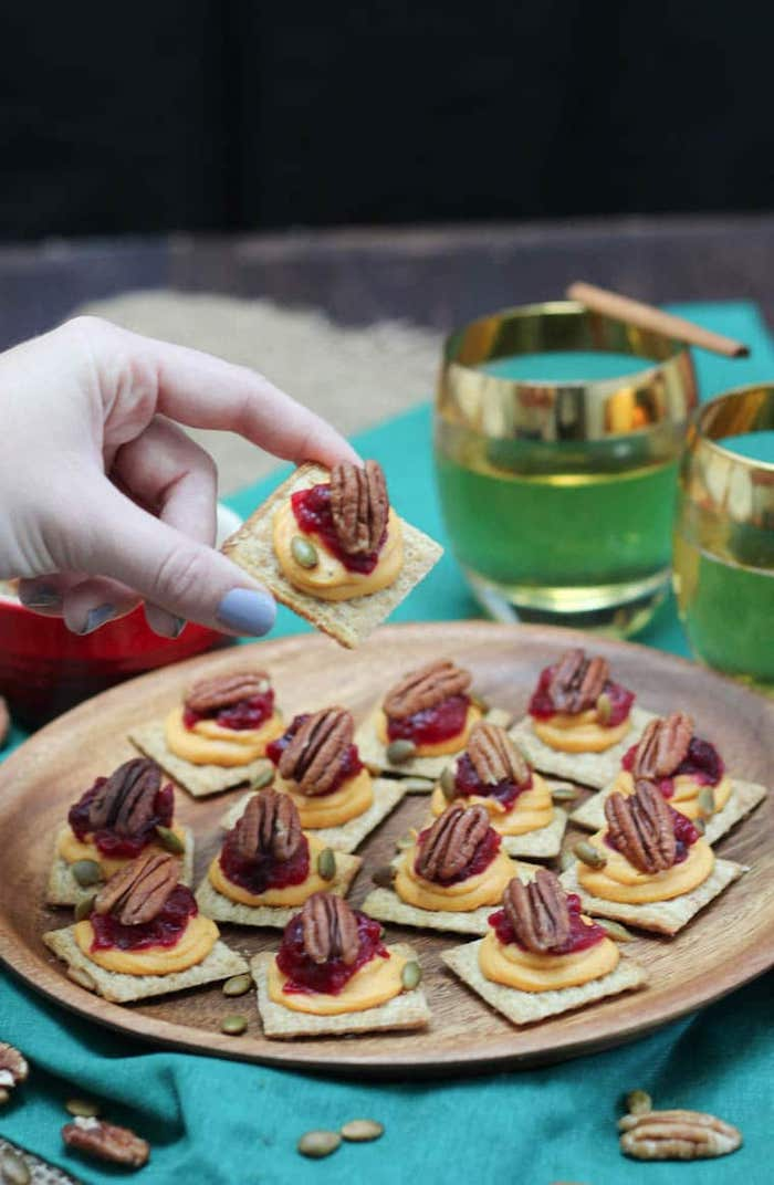 vegan bites, easy party snacks, crackers with sweet potato puree, cranberry sauce and walnuts, placed on wooden plate