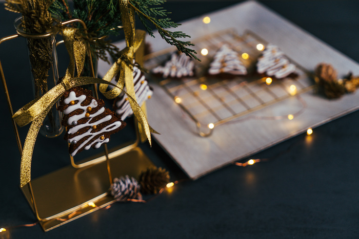 christmas tree shaped cookies, hanging with golden ribbon, vegan gingerbread cookies, lights around them