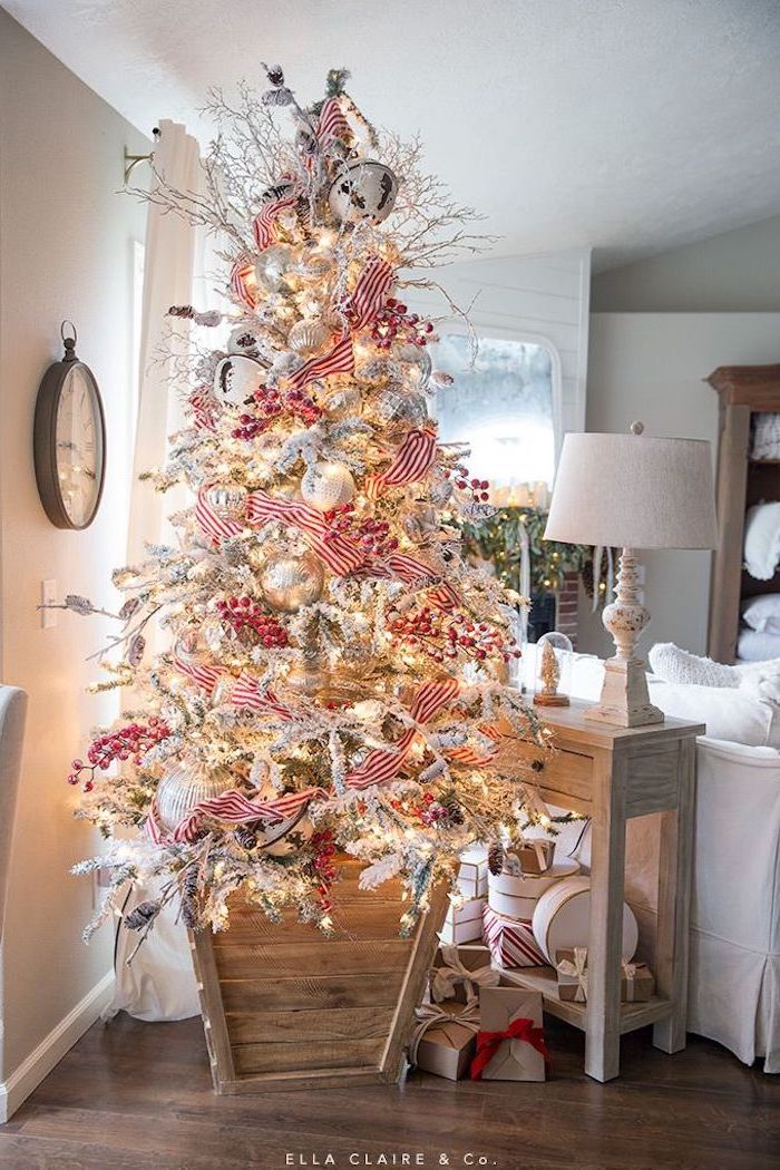 faux tree with faux snow, christmas decorations indoor ideas, red and white ribbon, white and silver ornaments